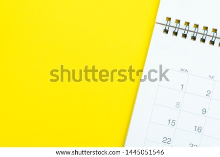 Flat lay of white clean desktop calendar on solid yellow background using as reminder, memo, meeting or project and work schedule concept.