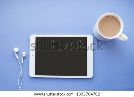 Flat lay of white tablet, earphones and a cup of coffee on purple background with copyspace.