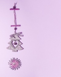 Flat lay of wooden christmas decoration tree with heart inside it and jingle bell and star with silver glitter on tips on purple. Christmas holidays concept from above with copy space
