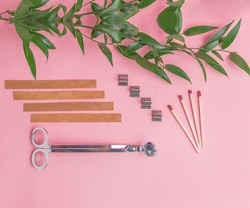 Flat lay of wooden wicks, scissors and wick holders on pink background. Nearby are matches and a branch with green juicy leaves