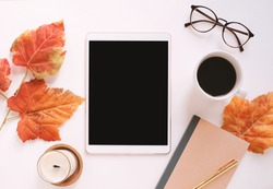 Flat lay of workspace desk on autumn leaves background with blank tablet, notebook, coffee and candle, lifestyle and seasonal concept, mockup style