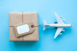 Flat lay of wrapped package with blank tag and airplane model on pastel blue background. Shipping logistics transport minimal creative concept.