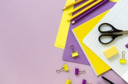 Flat lay of yellow and lilac school supplies on a color background. Space for text