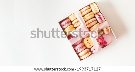 Flat lay of yellow and pink macaroons on the white background with a free space for text. Macro shot of French sweet dessert cookies arranged together in the gift box tied with a ribbon. Foto stock ©