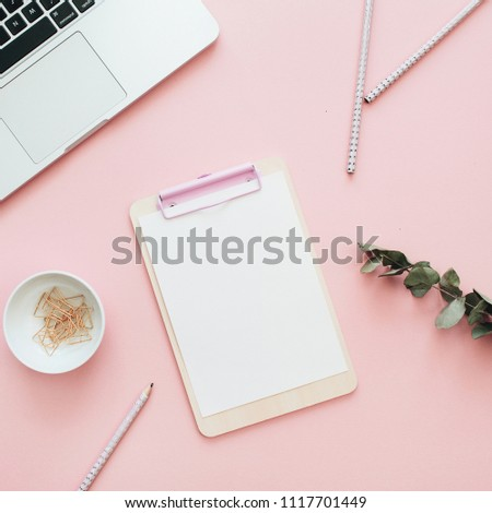 Flat lay office workspace with blank laptop, clipboard, eucalyptus branches on pink background. Top view minimal mock up template concept.