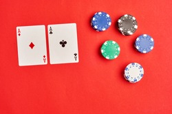 Flat lay or top view. Stack of chips and two aces on the table on the red background - poker game concept.