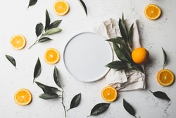Flat lay orange slices, orange tree eaves and empty plate. Copy space. top view.