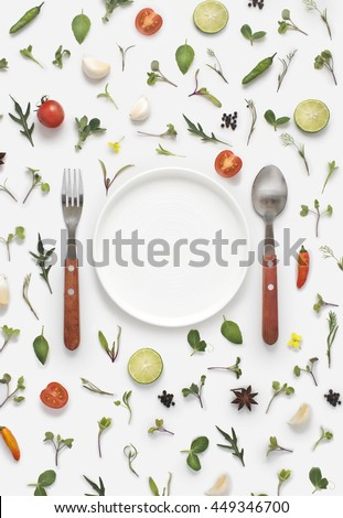 Flat lay overhead view cutlery set, plate and a blank text space invitation card on white background with vegetables, herbs and spices. Invitation or menu design background.