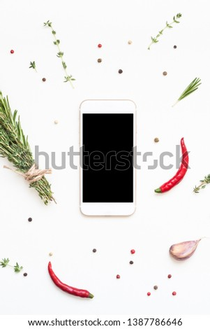 Flat lay overhead view smartphone mockup blank text space on white background with greens herbs and spices. Menu design food blog recipe cookbook or delivery app with cooking ingredients