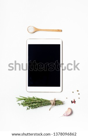 Flat lay overhead view tablet PC gadget mockup blank text space on white background with greens herbs and spices. Menu design food blog recipe cookbook or delivery app with cooking ingredients