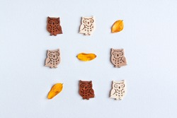 Flat lay pattern of cute wooden owls set with tree diferents colors of wood light to dark and orange autumn leaves on white background. Wood carving concept