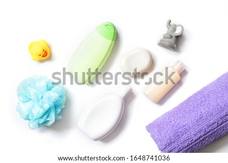 Flat lay photo baby care cosmetics, toiletries kit. Blue sponge, white shampoo bottle, green shower gel, body lotion, soap bar, rubber toys and purple cotton bath towel