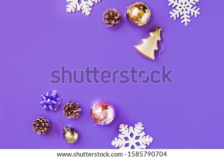 Flat lay photo gold and pink balls, yellow bauble, pine cones and snowflakes. Christmas tree decoration on a purple background. New Year banner and mockup. Free space for text #1585790704