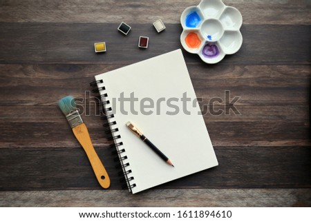 flat lay photo of a sketchbook and art supplies on a retro wood surface