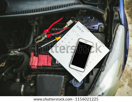 Flat lay photo of car maintenance appointment concept consist of smartphone, calendar, screwdriver, wrench on the engine and battery.