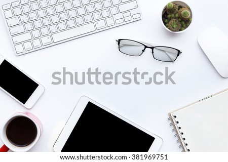 Flat lay photo of office desk with keyboard, notebook, tablet, smartphone, eyeglasses and red cup, top view