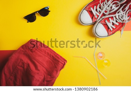 Flat lay photo, travel concept. Vacation equipment, stuff. Top view of red sneakers, red shorts and sunglasses on yellow background. Vacation clothes mockup. Free space for text