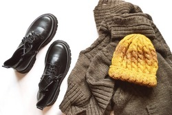 Flat lay photography fashion clothes fall winter season. Black ankle boots, brown woolen sweater and yellow knitted hat