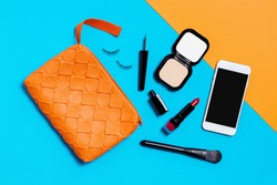 Flat lay photography with Orange make up bag, Cosmetics and smart phone, Overhead view of essential beauty items for woman
