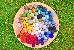 flat lay picture of many colorful and vibrant ravels of wool, laying in a large wooden bowl standing on the ground of green grass