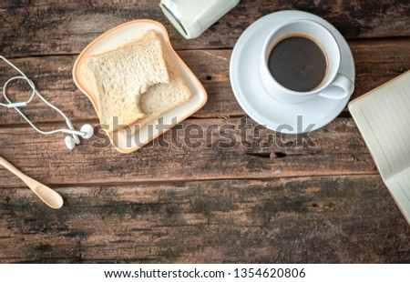 Flat lay picture of morning breakfast set which comprises of bread, bottle of milk and black hot coffee. Chilling out at home concept. The wood background has blank copy space to add notes or text.