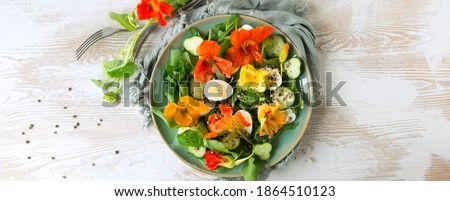 flat lay plate of salad with eggs, cucumbers and edible nasturtium flowers on light wooden table, space for text Stockfoto ©
