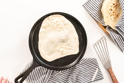 Flat lay. Preparing homemade flatbread on a cast-iron skillet.