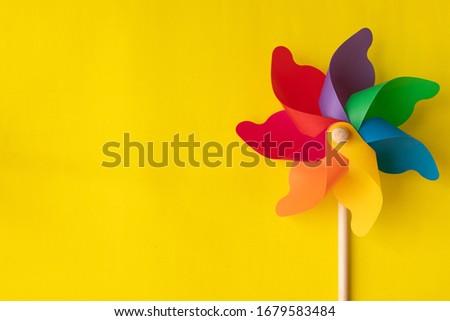 Photo of  Flat lay Rainbow pinwheel on yellow background, copy space.