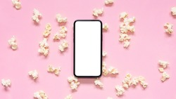 Flat lay scattered popcorn with mobile phone with blank screen on pink background. Mockup phone with white copy space. Smartphone application for online cinema, films and media.