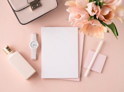 Flat lay scene in peach pink tones for self employed freelance girl. Feminine little things as a small bouquet, cosmetic bottle, bag and white watch. Sketch Pad or notebook mockup.