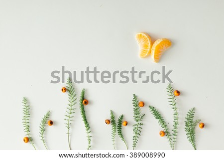 Flat lay setup made of tangerine and green grass on white background.