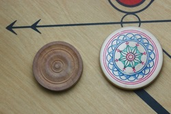 Flat lay shot of white carrom men and striker on the carrom board with selective focus.