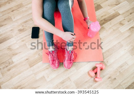Flat lay sport photography. Female athlete  relax after workout. Fitness flat lay photography of  coach after training. Girl drinks healthy protein shake after workout.