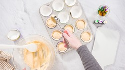 Flat lay. Step by step. Scooping cupcake batter into a foil cupcake liners to bake vanilla Mardi Gras cupcakes.