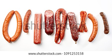 Flat lay still life of a selection of spicy dried or smoked beef and pork sausages isolated on white in a panorama banner