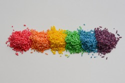 flat lay style photo of colorful rice with bright colors and texture, laid out in a rainbow with white background, child's sensorial play