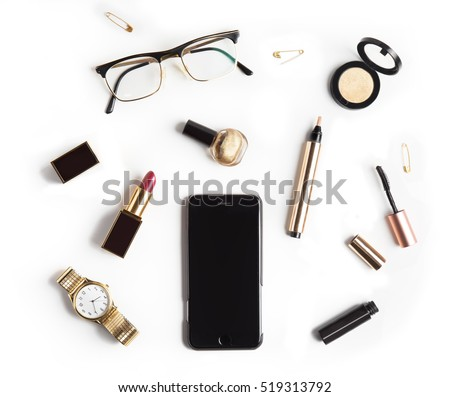 Flat lay, top view feminine table desk isolated on white.  Workspace with cosmetics, phone, glasses, lipstick, nail lacquer, watches, mascara and eyeshadow in gold. Golden and black tones.