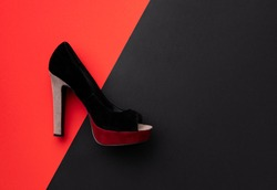 Flat lay top view minimal composition with shoe on double red and black background. Spring summer shopping sale template with copy space.