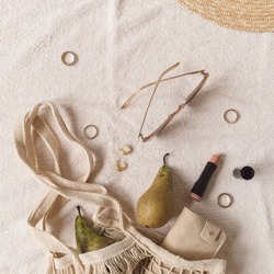 Flat lay, top view neutral fashion composition with women's accessories and bijouterie on beige blanket. String bag, straw hat, sunglasses, lipstick, rings, earrings, pears. Minimal lifestyle concept.