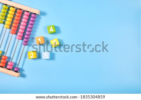Flat lay, Top view of bright colored wooden bricks and abacus toy background with copy space for text, Numeral cubes with numbers 1 to 5 & colorful abacus, Child development, early math skills concept Сток-фото ©