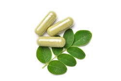 Flat lay (top view) of Dried Moringa leaves powder capsules with fresh green leaves  isolated on white background.