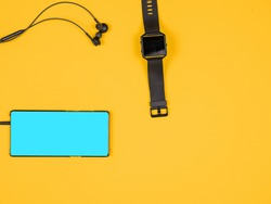 Flat lay top view of smartphone with headphones in it and smartwatch. Design and concept. Orange background
