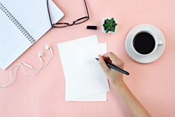 Flat lay, top view office desk. Hand holding pen writing on blank paper. Coffee, notebook, earphone, eyeglasses, green plant on pink background.