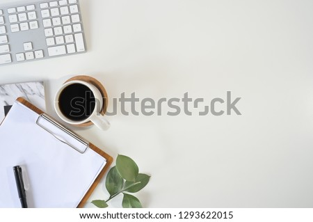 Flat lay top view office desk. Workspace with blank clip board, computer keyboard, office supplies, pen, green leaf, and coffee cup on white background. #1293622015