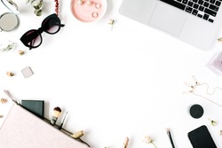Flat lay, top view office table desk frame. feminine desk workspace with laptop, clutch, cosmetics, phone, sunglasses, lipstick rose buds on white background.