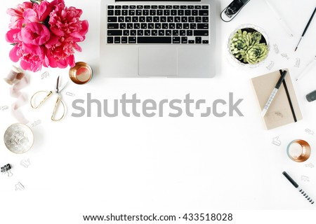 Flat lay, top view office table desk. Workplace with laptop, succulent, peonies, golden scissors, spool with beige ribbon, pencils and diary.