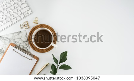 Flat lay, top view office table desk. Workspace with blank clip board, keyboard, office supplies, pencil, green leaf, and coffee cup on white background. stock photo