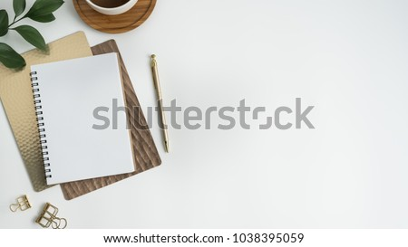 Flat lay, top view office table desk. Workspace with blank clip board, keyboard, office supplies, pencil, green leaf, and coffee cup on white background.