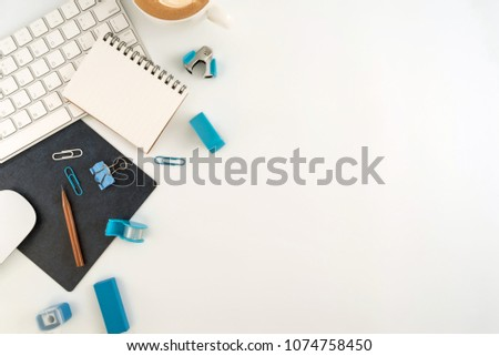 Flat lay, top view office table desk. Workspace with blank note book, keyboard, Blue office supplies and coffee cup on white background.