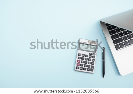 Flat lay, top view office table desk. Workspace with calculator, black pen , laptop on the indigo blue background.Copy Space for text,Empty Blank to word.Business Finance,Education Technology Concept.